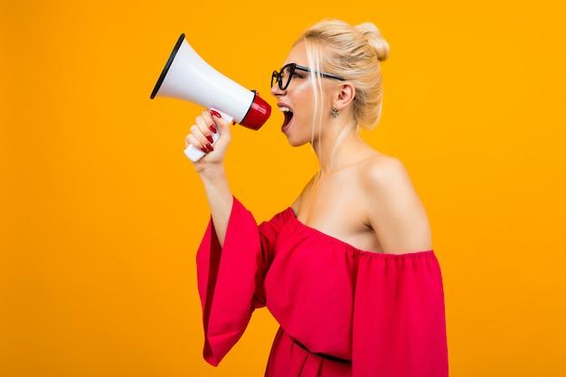 Chica con un altavoz se encuentra de lado sobre un fondo amarillo studio Foto Premium
