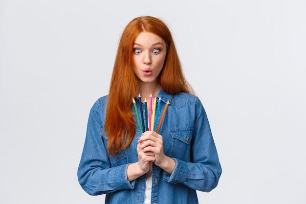 Chica ansiosa por comenzar un nuevo curso de arte, aprender a diseñar, hacer modelos, pararse con lápices de colores Foto Premium