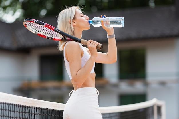 Chica apta con raqueta de tenis sedienta Foto gratis