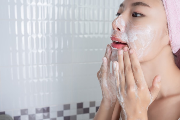 Chica asiática se lava la cara. Foto gratis