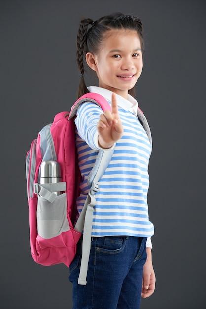 Chica asiática con mochila de pie y mostrando un dedo índice a la cámara Foto gratis
