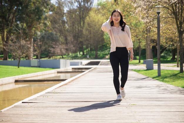 Chica asiática positiva en su camino a través del parque de la ciudad Foto gratis