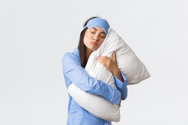 Chica asiática tonta y linda con máscara de dormir azul y pijama, abrazando la almohada con fuerza como un despertar involuntario, no quiere levantarse de la cama por la mañana, durmiendo pesado posando sobre fondo blanco. Foto Premium