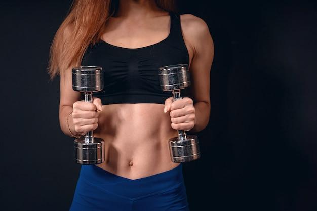 Chica atlética levanta pesas. ejercicio para bíceps con pesas. con espacio de texto libre Foto Premium