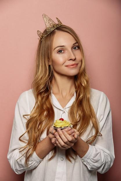 Chica atractiva con una corona y cupcake Foto gratis