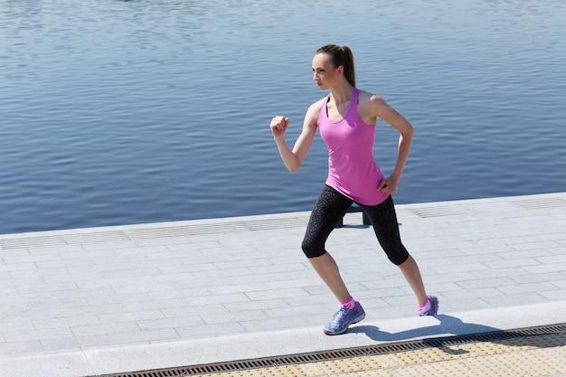 Chica atractiva corriendo en la calle Foto gratis