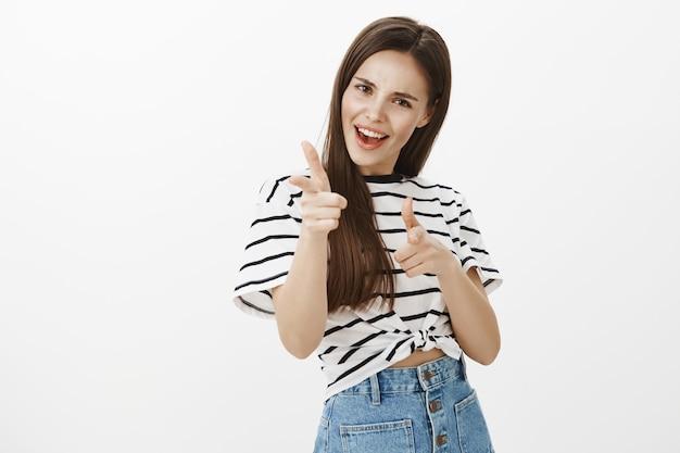 Chica atractiva descarada y emocionada señalando con el dedo, felicitaciones, gesto de felicitaciones, alabando a la persona Foto gratis