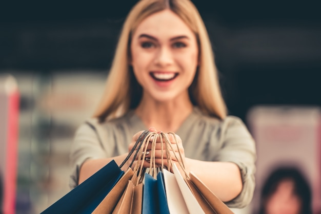 Chica atractiva es la celebración de bolsas de la compra. Foto Premium