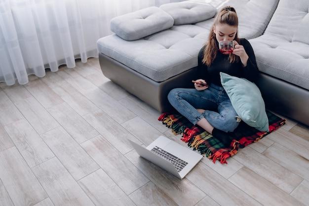 Chica atractiva joven en casa trabajando con un ordenador portátil y hablando por teléfono. comodidad y comodidad en casa. oficina en casa y trabajo desde casa. empleo remoto en línea. Foto gratis
