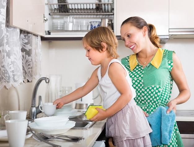 Chica ayudando a mamá a lavar los platos Foto gratis