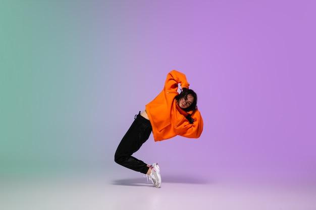 Chica bailando hip-hop en ropa elegante sobre fondo degradado en el salón de baile en luz de neón. Foto gratis