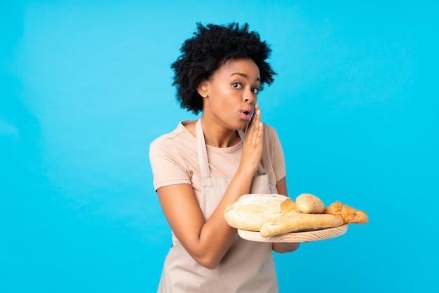 Chica baker cogiendo panes sobre fondo azul. Foto Premium
