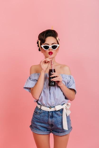 Chica Bien Formada En Pantalones Cortos De Mezclilla Y Blusa A Rayas Bebiendo Bebidas Foto De Estudio De Dama Pinup En Gafas De Sol Foto Gratis