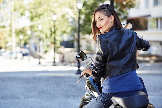 Chica biker en una chaqueta de cuero en moto Foto gratis