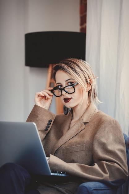 Chica en blazer y gafas trabajando con computadora portátil Foto Premium