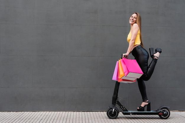 Chica con bolsas de compras en scooter eléctrico Foto gratis