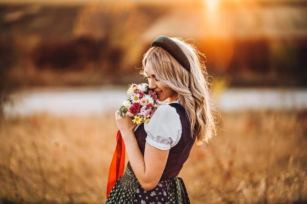 Chica bonita rubia en dirndl, de pie al aire libre en el campo, con ramo de flores de un campo. Foto Premium