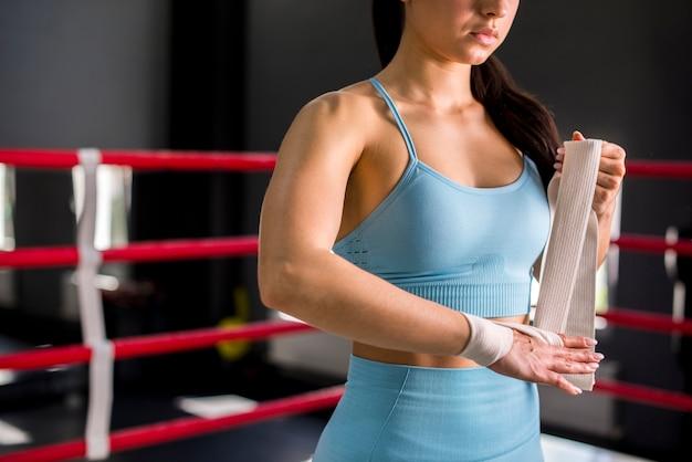 Chica boxeadora posando en el gimnasio Foto gratis