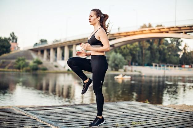 Chica calentando en la plataforma de madera en la orilla del río | Foto  Premium