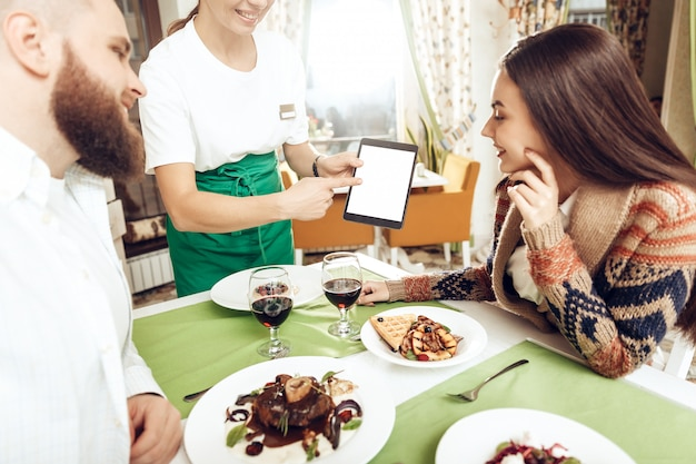 Chica camarera toma un pedido de una pareja joven Foto Premium