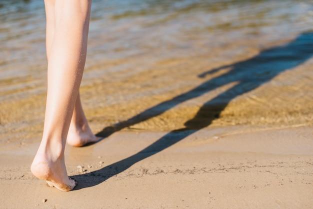 Chica caminando descalza sobre la arena hasta la costa Foto gratis