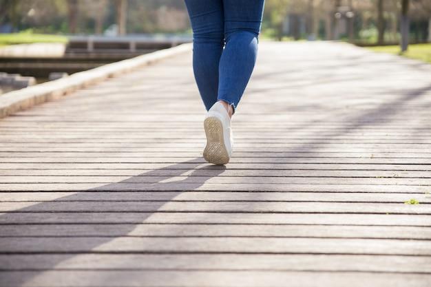 Chica caminando por el sendero en el parque de la ciudad Foto gratis