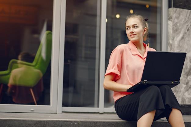 Chica en una camisa rosa sentada cerca de casa y usar la computadora portátil Foto gratis
