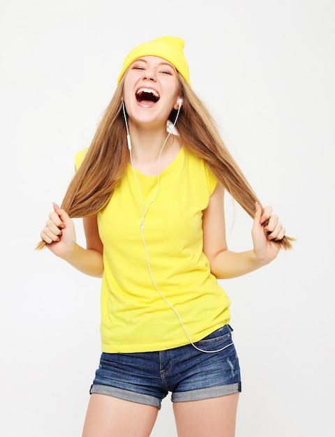 Chica en camiseta amarilla bailando con expresión de la cara inspirada. Foto Premium