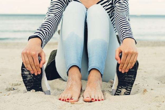 Chica en camiseta a rayas y jeans se sienta descalza en la playa al lado de los zapatos Foto Premium