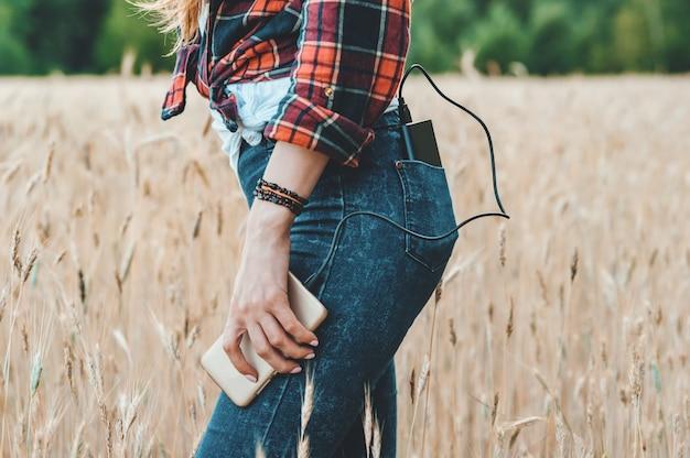La chica en el campo amarillo, carga el teléfono del banco de poder. Foto Premium