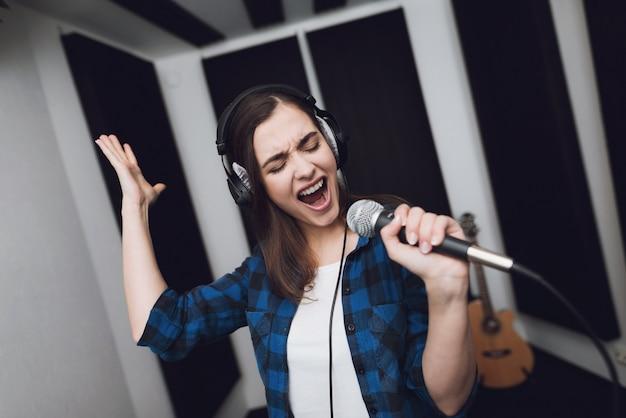 Chica canta su canción en un estudio de grabación moderno. Foto Premium