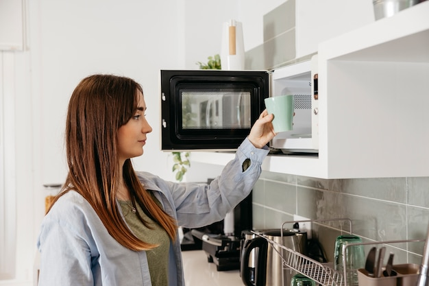 Chica casual con microondas para calentar la taza Foto gratis