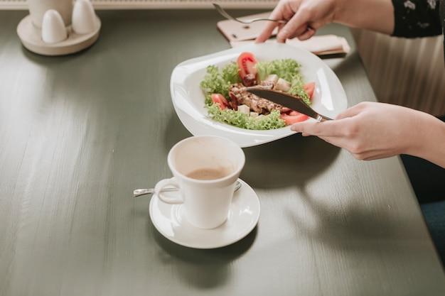 Chica comiendo una ensalada en un restaurante Foto gratis