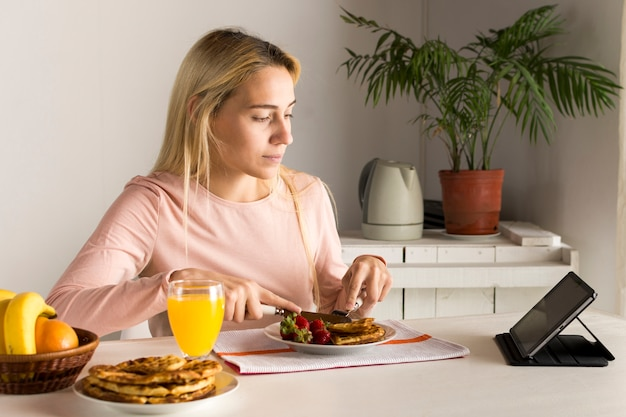 Chica comiendo gofres viendo tablet Foto gratis
