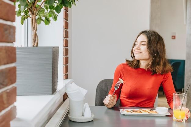 Chica comiendo en un restaurante Foto gratis