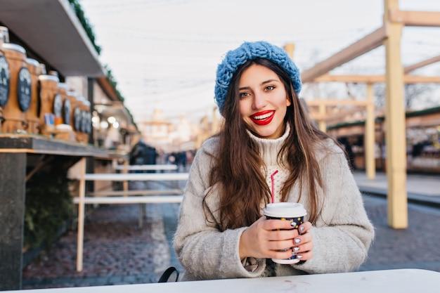 Chica complacida con cabello largo oscuro sonriendo en la calle mientras toma café. linda mujer joven en abrigo y suéter posando con una taza de té en un día frío en la ciudad. Foto gratis