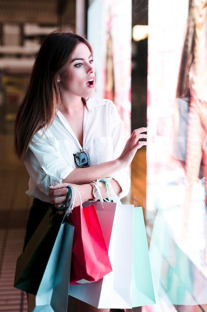 Chica de compras mirando escaparate Foto gratis