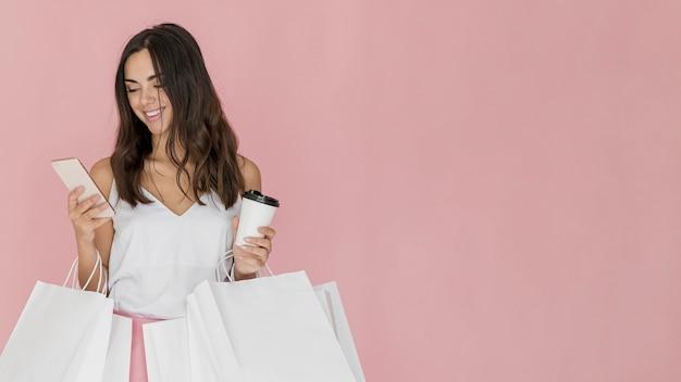 Chica comprensiva con muchas redes de compras. Foto gratis