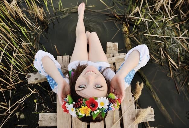 Chica en una corona de flores en su cabeza sentada en el puente y moja los pies en el río Foto Premium