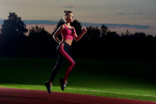 Chica corriendo por la noche en el estadio preparándose para el maratón. Foto Premium