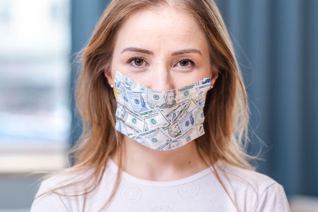 Chica en cuarentena con una máscara de dinero Foto gratis