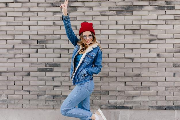 Chica delgada en jeans de moda divirtiéndose en la calle en un día frío de primavera. modelo de mujer dichosa en traje de mezclilla bailando en la pared urbana y agitando las manos. Foto gratis