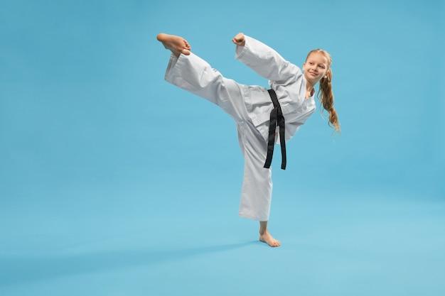 Chica deportiva activa en kimono pateando con pierna en estudio Foto gratis