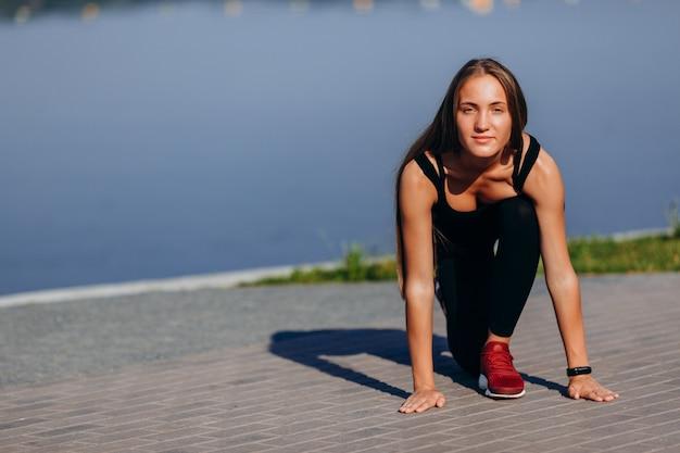 Chica deportiva calentando al aire libre y estirando las piernas mirando a la cámara Foto Premium