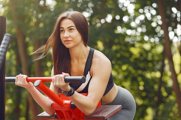Chica deportiva en un entrenamiento top negro en un parque de verano Foto gratis