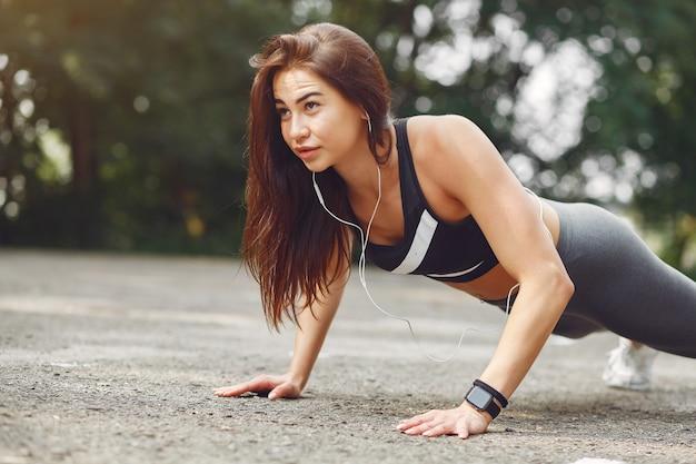 Chica deportiva entrenando con auriculares en un parque de verano Foto gratis