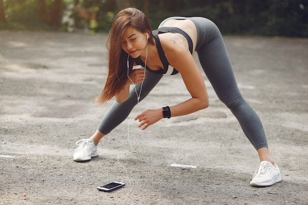 Chica deportiva entrenando con teléfono y auriculares Foto gratis