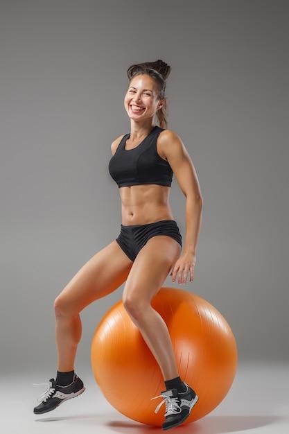 Chica deportiva haciendo ejercicios en un fitball Foto gratis