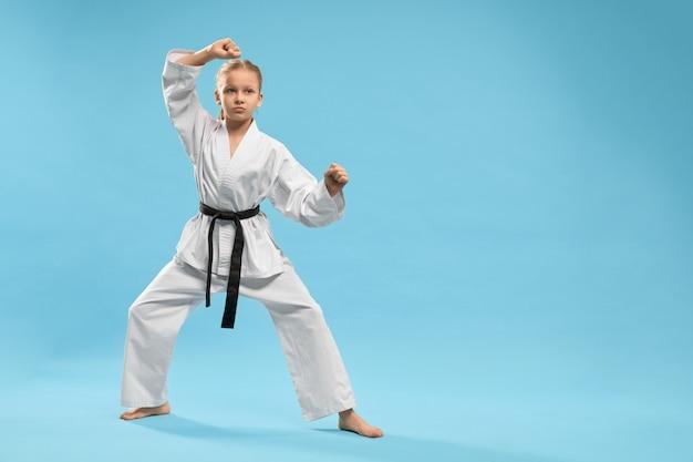 Chica deportiva de pie en posición y entrenamiento de karate en estudio Foto gratis