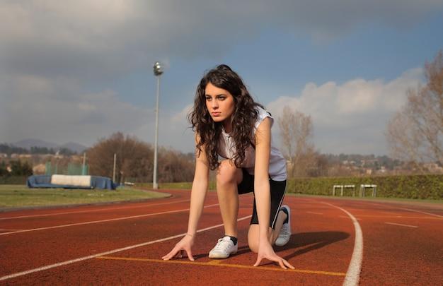 Chica deportiva en una pista de atletismo Foto Premium